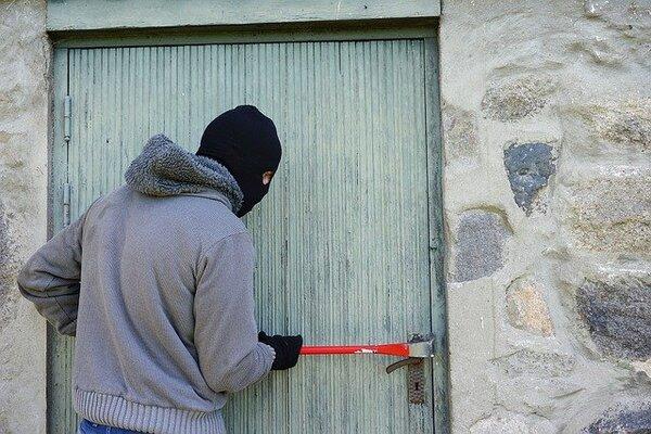 zlodej snažiaci sa dostať do domu