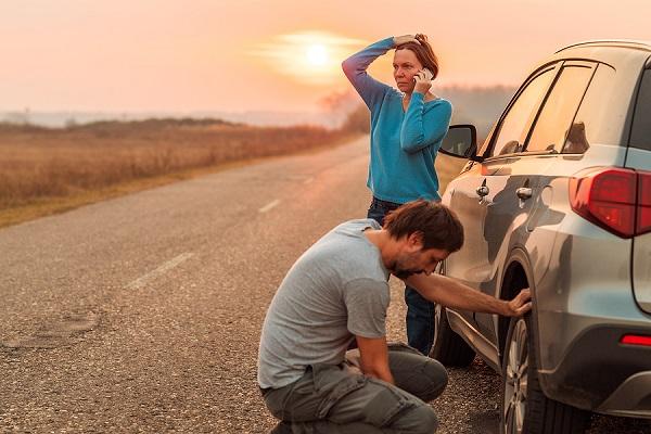 žena a muž na ceste opravujú defekt